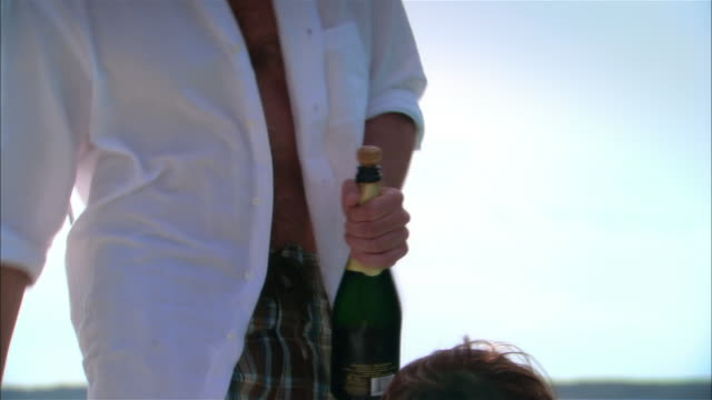 Close-up Couple opening champagne bottle on boat deck/ Harbor Island, Bahamas