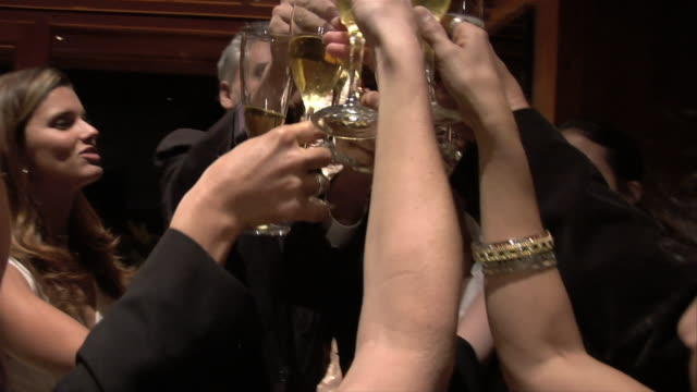 Close-up Couples drinking a champagne toast and celebrating at Christmas party