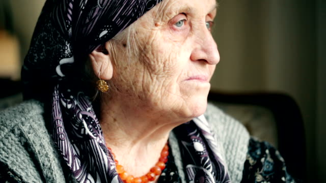 Close-up footage of an elderly woman looking away
