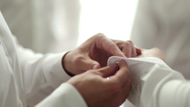 Close-up footage of male hands dressing groom. Man is adjusting cufflinks.