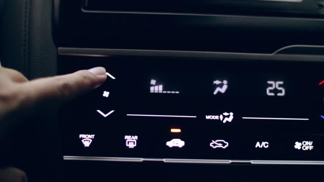 Close-up Hand anpassen Button Control Klimaanlage auf einem Armaturenbrett