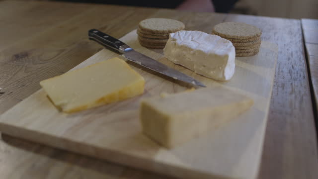 Close-up, handheld shot of a cheese board on a communal table, UK.