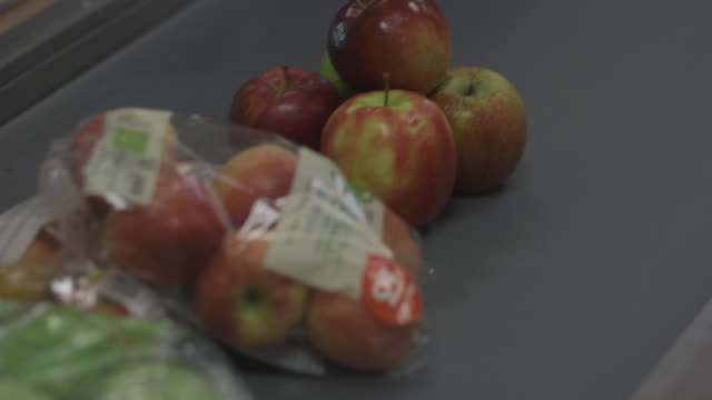 Close-up, high-angle shot of apples on a moving supermarket conveyor belt, UK.
