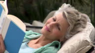 Close-up Mature woman reading book and reclining in lounge chair on patio/ San Antonio, Texas, USA