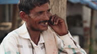 Close-up of a adult man talking on a mobile phone, Haryana, India