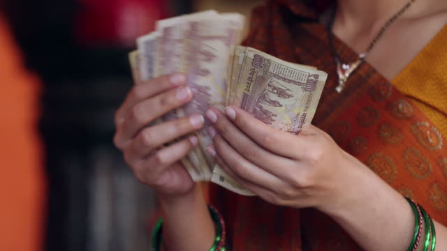 Close-up of a adult woman counting indian rupees note, Delhi, India