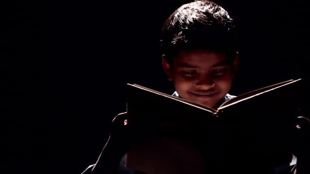 Close-up of a boy reading a book