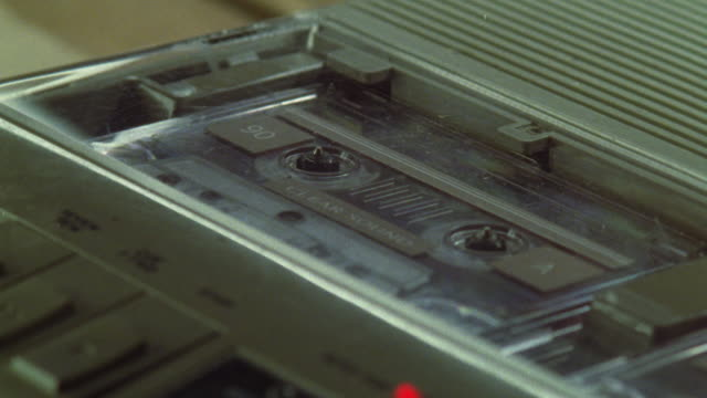 Close-up of a cassette tape being played in a tape recorder.