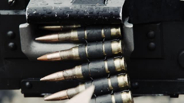Close-up of a chain of bullets going through a belt-fed machine gun.