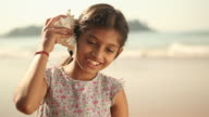 Close-up of a girl listening to conch shell on the beach