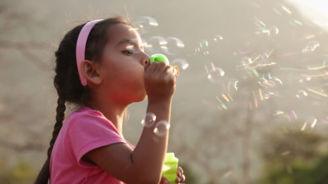 Close-up of a girl playing with a bubble wand