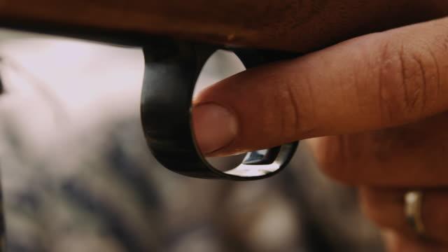 Nahaufnahme von einem Jagdgewehr aufgehoben wird, und der Schütze seinen Finger am Abzug, schussbereit zu platzieren.