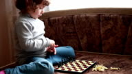 Close-up of a little girl arranging black pawns on the board