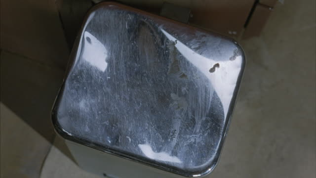 Close-up of a man opening a garbage can with a metal lid and throwing away papers.