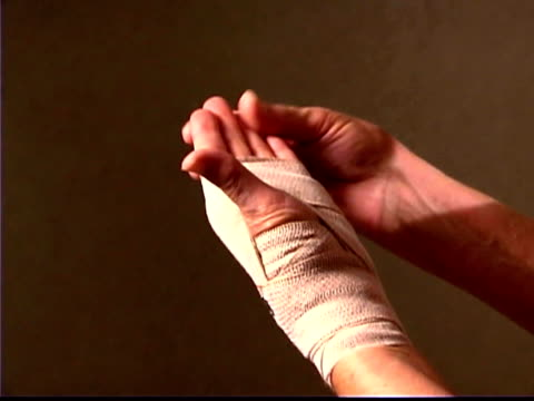 Close-up of a patient checking her hand after it has been wrapped.