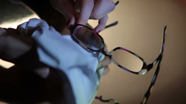 Close-up of a person cleaning her eyeglasses