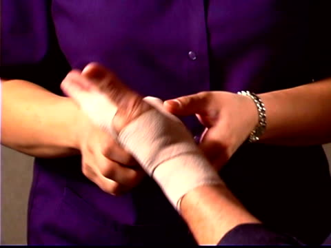 Close-up of a physical therapist wrapping a patient's wrist with an ace bandage.