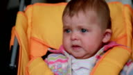 Close-up of a sad baby sitting in the pram