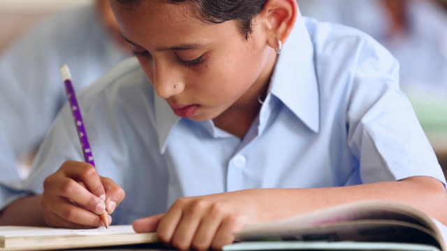 Close-up of a schoolgirl studying in the classroom, Haryana, India