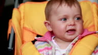 Close-up of a serious baby sitting in the pram