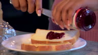 Close-up of a woman spreading jelly on bread while making a peanut butter and jelly sandwich.