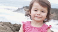 Close-up of a young girl smiling on a beach