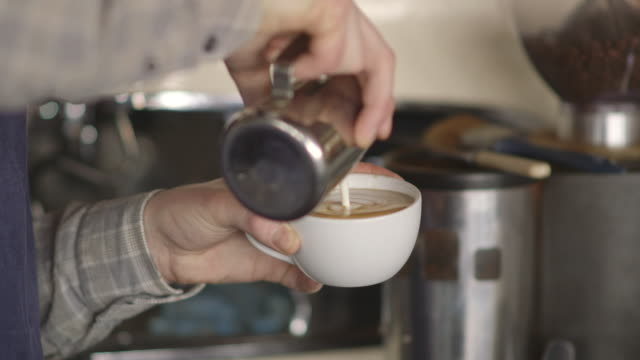 Close-up of a young man pouring heated milk into coffee creating leaf-shaped latte art, UK.