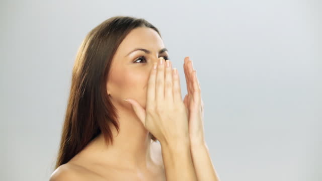 Close-up of a young woman applying moisturizer on he face