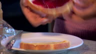 Close-up of a young woman?s hands assembling her sandwich and cutting it diagonally.