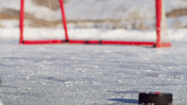 Close-up of an outdoor ice rink, hockey net, and skates.