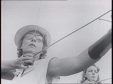 Closeup of archer May Marshall firing arrow / she gathers her arrows 6 bullseyes from the target / smiles to camera