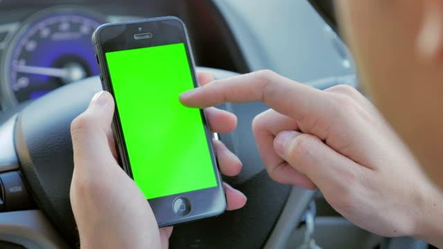 Nahaufnahme der Geschäftsmann mit smartphone, Green-screen im Auto