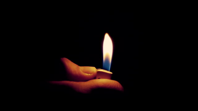 Close-up of Cigarette Gas Lighter in Hand on Black background