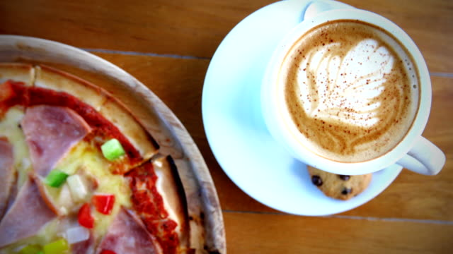 Close-up of Coffee cup and freshly baked pizza.