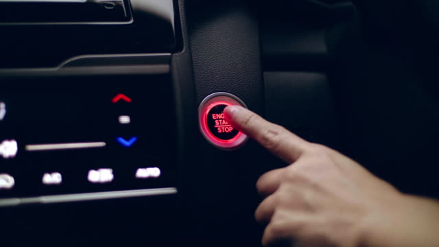 Close-Up Of Female Finger Pushing Car Start-Stop Light Button On A Vehicle's Dashboard