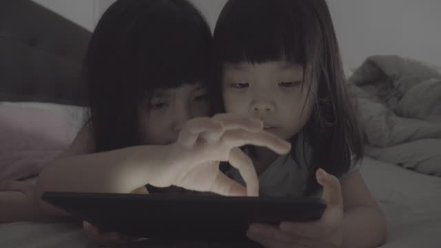 Closeup of girls using tablet in bed