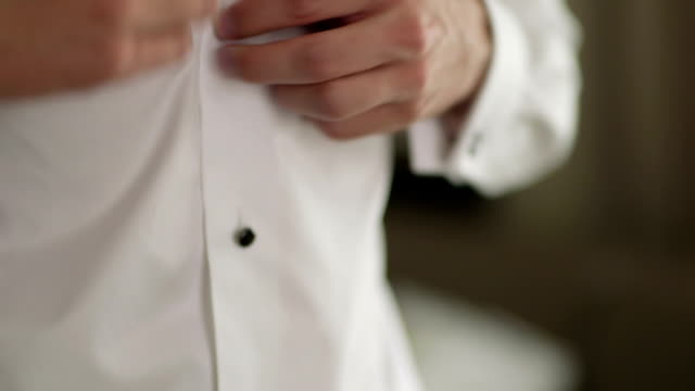 Closeup Of Groom Buttoning Shirt During Wedding