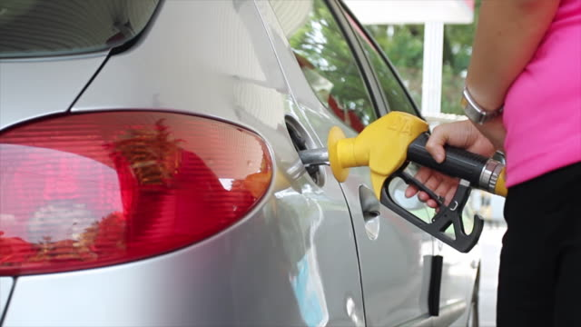 Closeup of hand refilling the car with fuel.