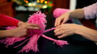 Close-up of hands braiding wool to create a teddy octopus.