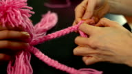 Close-up of hands making a plait in wool