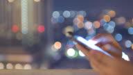 Nahaufnahme der Hände berühren Smartphone auf dem Dach mit Kreis Bokeh Licht der Stadt bei Nacht Zeit