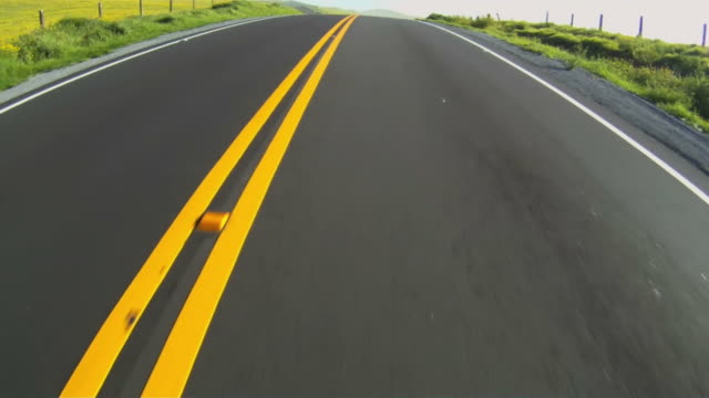 Close-up of highway while moving along divided yellow line