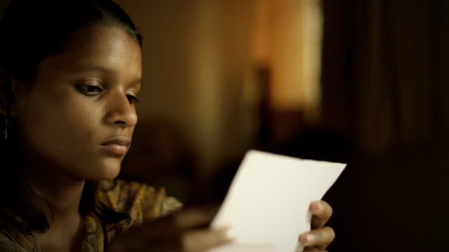 Close-up of Indian girl smiling while reading letter