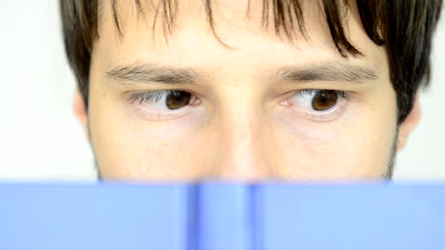 Close-up of Man's eyes reading blue book quickly