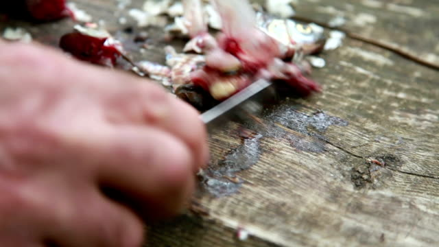 Close-up of mans hands cleaning the fish guts from the wooden cutting board