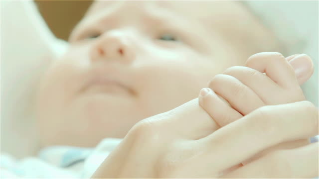 SLO MO & Close-up of Newborn baby holding mother's finger