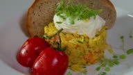 Closeup of poached egg grilled tomatoes smoked fish kedgeree on sourdough toast garnished with sprouts