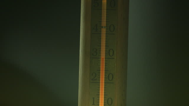 Close-up of red alcohol 'mercury' in a wooden metric thermometer rising from 24 to 38 degrees Celsius.