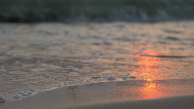 Close-up van zee golven op Sandy Beach bij zonsondergang