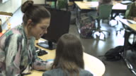 Close-up of teacher helping student in a classroom